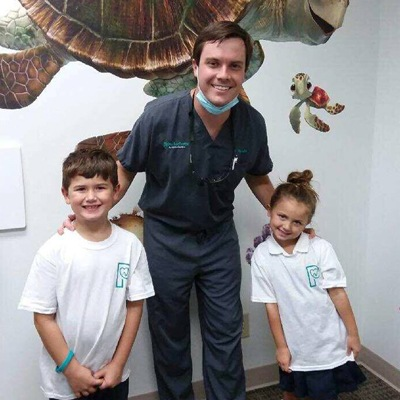 Dr. Lee Redditt posing with two young patients.