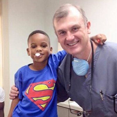 Dr. Hube Parker smiling with a young patient.