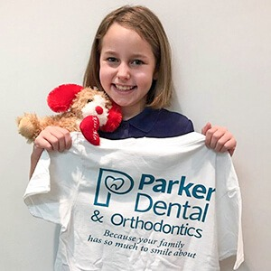 young woman holding Parker dental shirt