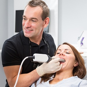 A dentist taking a digital scan of a patient's mouth