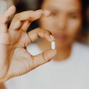 person holding a small pill