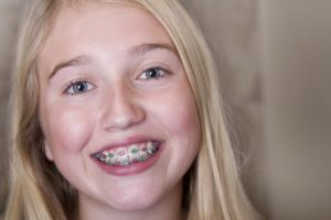 girl blonde hair braces smiling