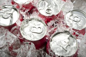 A six pack of soda underneath ice.