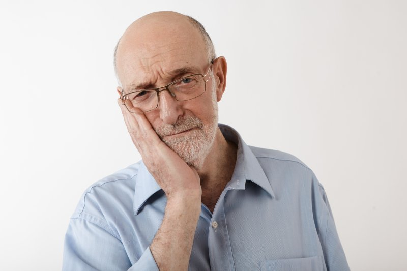 older man bald head holding jaw from tooth pain