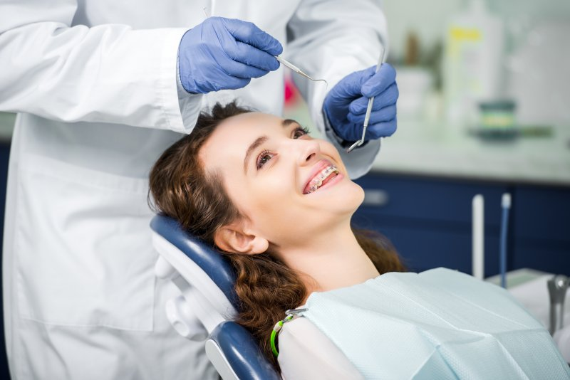a female patient wearing braces receiving care by an orthodontist in West Mobile