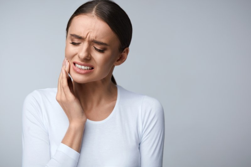 Woman with tooth sensitivity needing to see emergency dentist