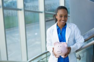 dentist in West Mobile holding pink piggy bank