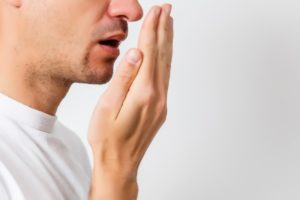 Man smelling bad breath while wearing a white t shirt