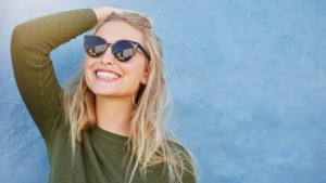 woman with sunglasses smiling after teeth whitening