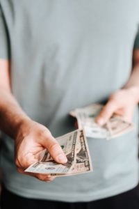 Man paying for the cost of root canals